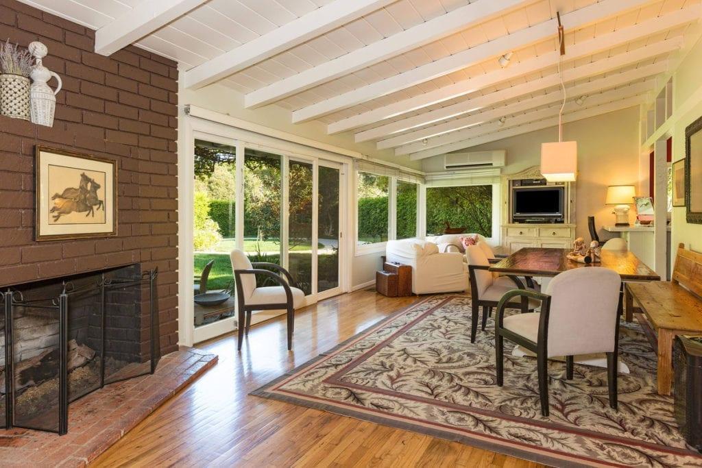 El salón de la cabaña, con enormes cristaleras que dan al jardín, chimenea y techo abuhardillado