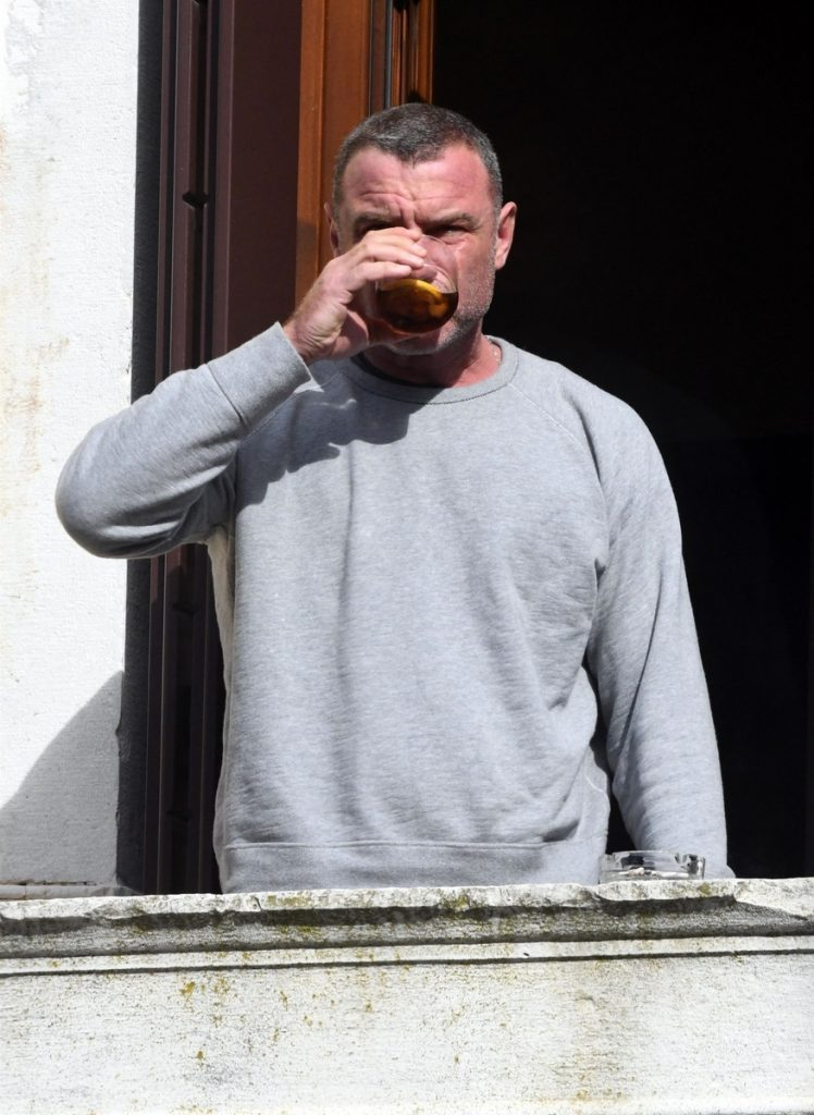 Liev toma una copa asomado al balcón de su residencia