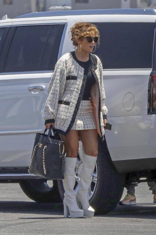 Este total look de Chanel está entre los looks más sexys de JLo: chaqueta y minifalda, top, maxibolso negro y botas blancas con plataforma