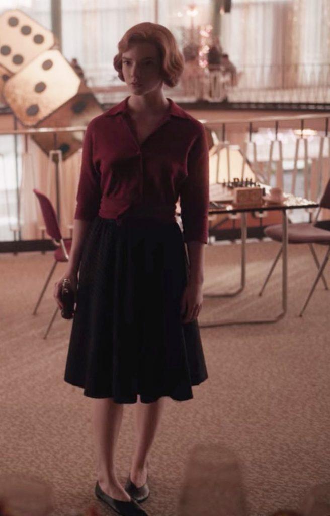 Beth Harmon, con blusa granate y falda negra