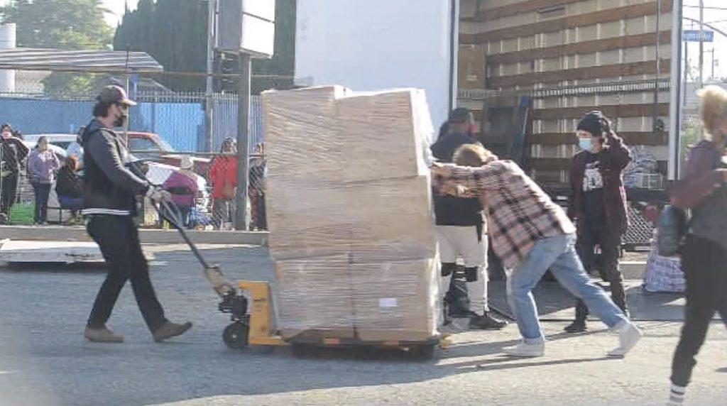 Un Brad Pitt más solidario que nunca ayuda a empujar las cajas para subirlas a una carretilla hidráulica
