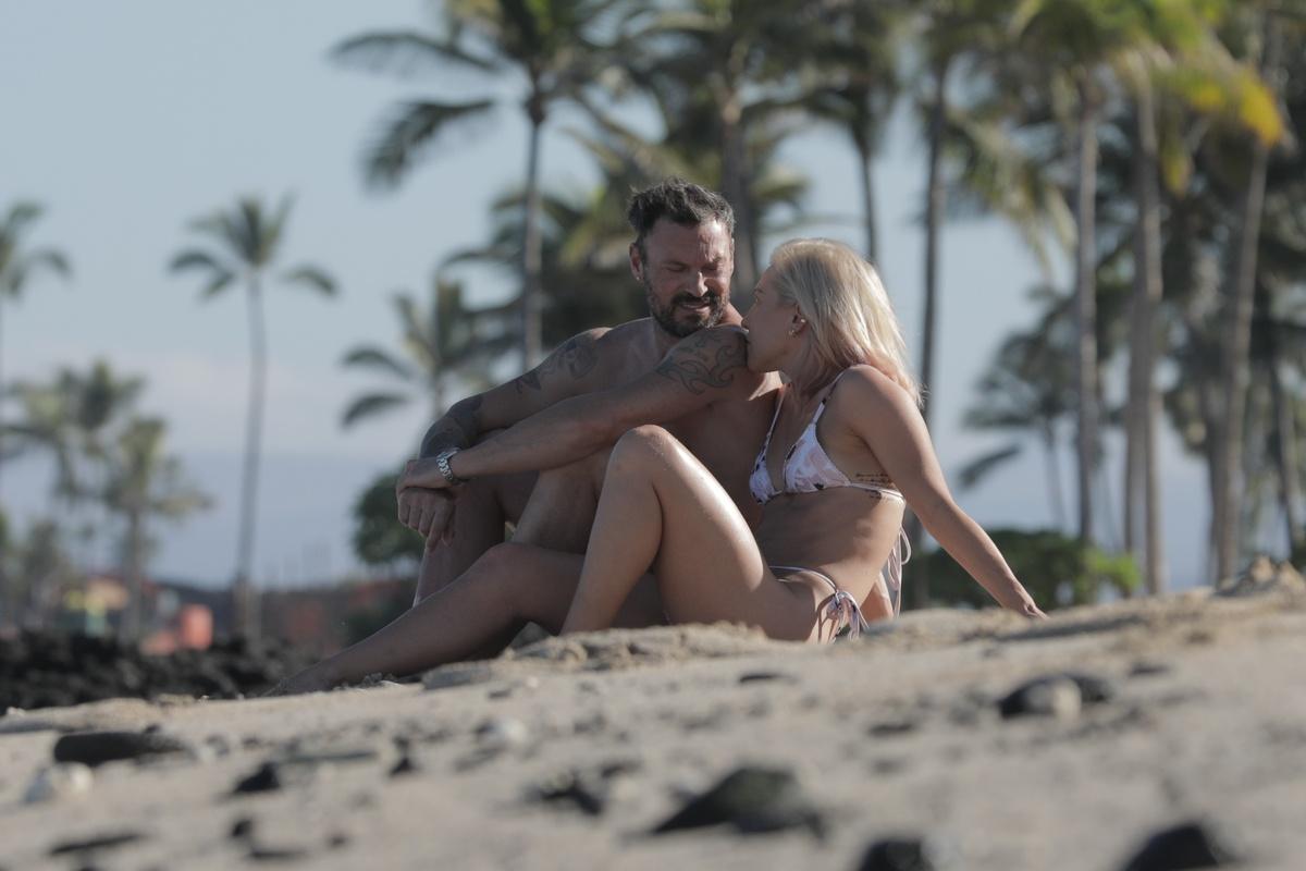 Brian Austin Green y su nueva novia sentados en la playa
