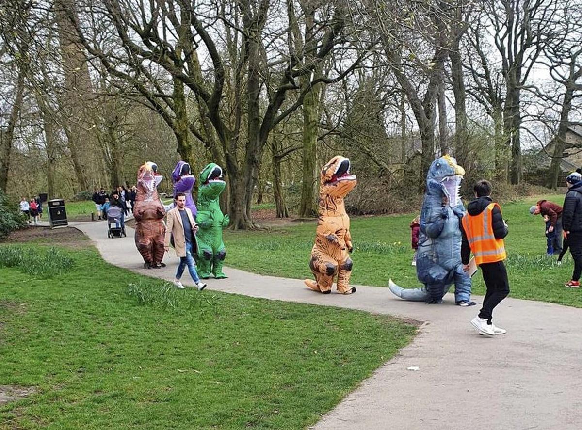 Varias personas disfrazadas de dinosaurio en un parque