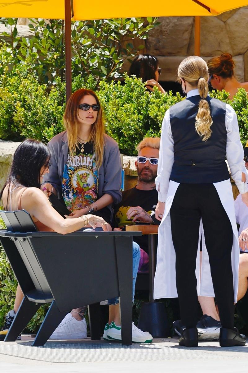 Behati, Adam y acompañantes con una camarera en la terraza