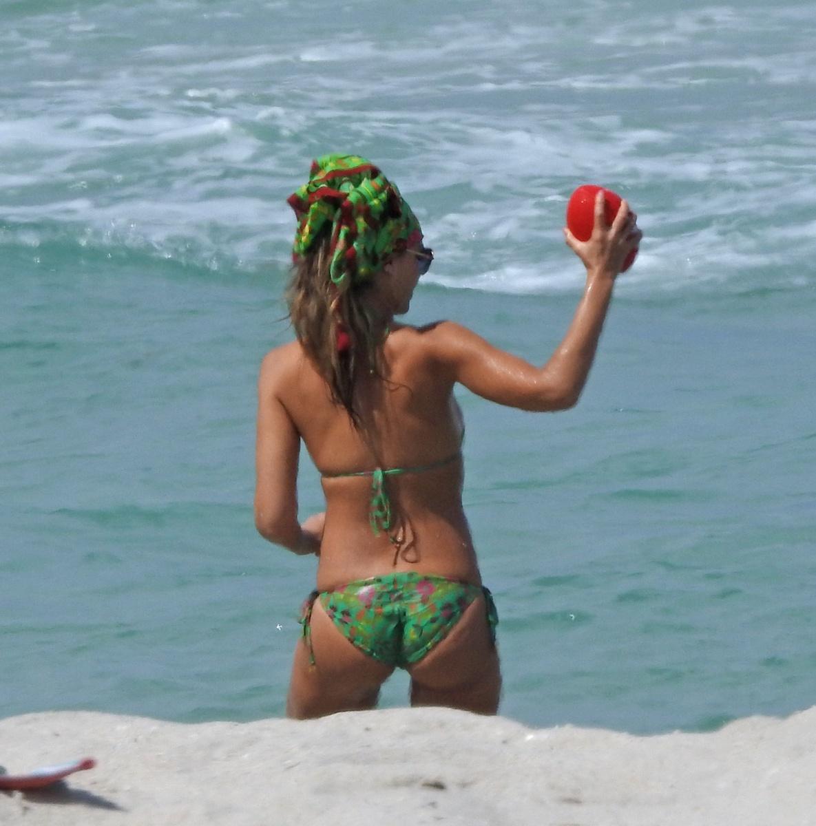 Jessica Alba en bikini verde con una pelota de rugby
