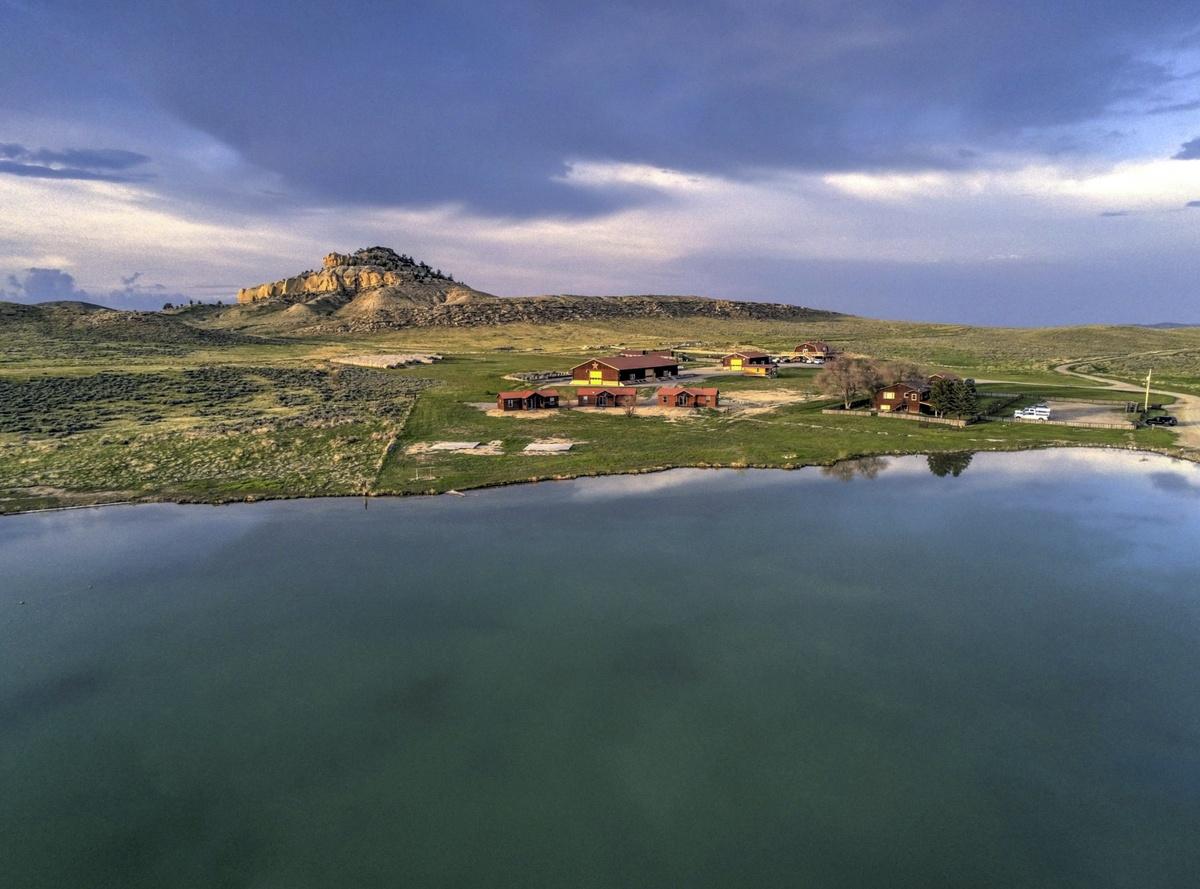 Panorámica del rancho con una colina al fondo y el lago en primer plano