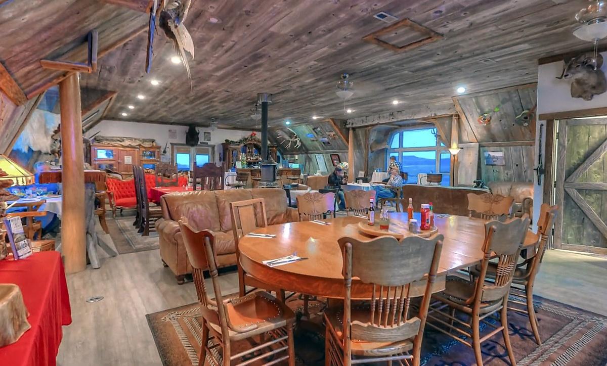 Una de las salas del rancho en el que Kanye West vivió su divorcio de Kim Kardashian y ahora vende: hay varias mesas de comedor, sofás viejos y esqueletos de animales colgados