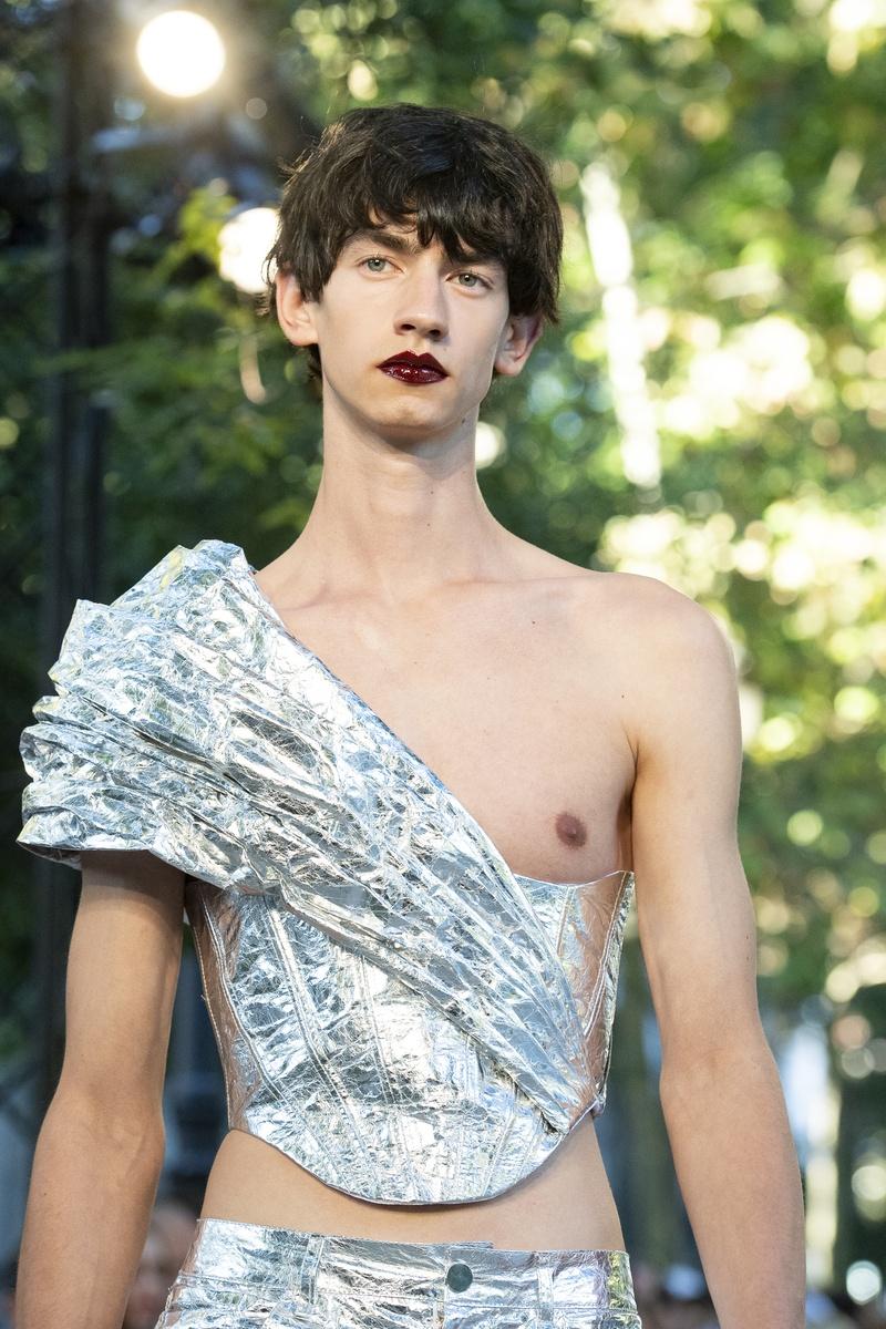 Modelo desfilando con corsé y pantalón plateados.